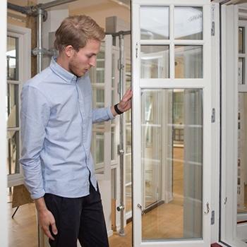 Medarbetare visar fönster i hantverkarhusets utställning